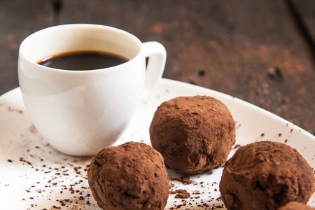 truffles sprinkled with cocoa on a plate with a cup of coffee Stock Photo