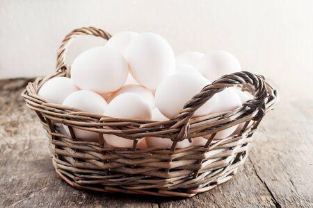 木製の背景上のバスケットの鶏の卵。