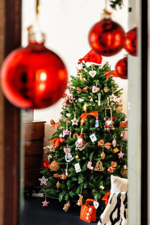 balls decorated: on a background of red balls decorated Christmas tree is visible. Stock Photo
