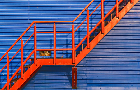 metallic stairs: part of red fire escape on the blue wall. Stock Photo