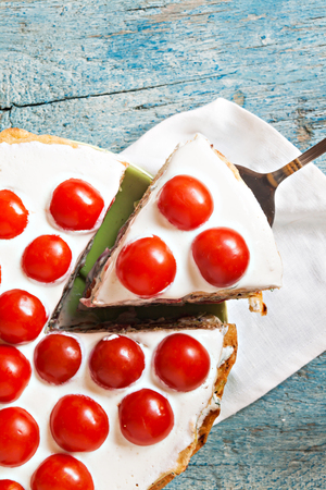 zucchini cake with tomato and parsley on a blue wooden background Stock Photo