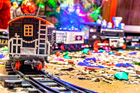 Christmas toy railroad near a Christmas tree with lights. Stock Photo