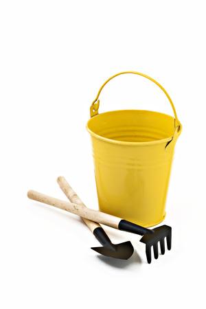 garden shovel, rake and yellow metal bucket isolated.