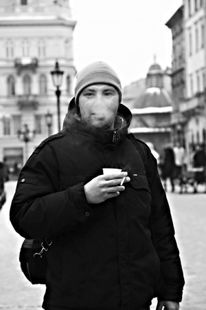 blinder: young man exhales smoke and drink coffee.