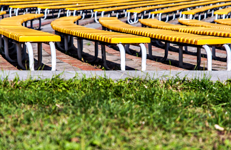 neat rows of green benches on a background of green grass Stock Photo
