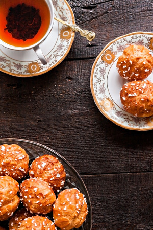 profiteroles topped with sugar and vintage cup with tea on a dark background.