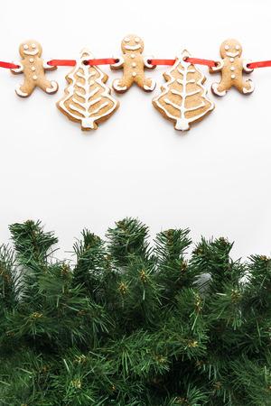 galleta de jengibre: pintado por galletas de jengibre en una cinta aislada en las ramas de abeto. Foto de archivo