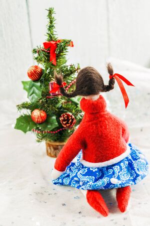 soft textile: Soft textile doll near a Christmas tree with gifts.