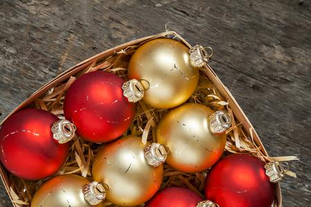 Bolas de Navidad rojo y oro en una vista superior de la cesta de madera de estilo vintage.