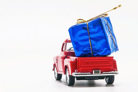 Ramassage de voiture rétro rouge avec un coffret bleu isolé.