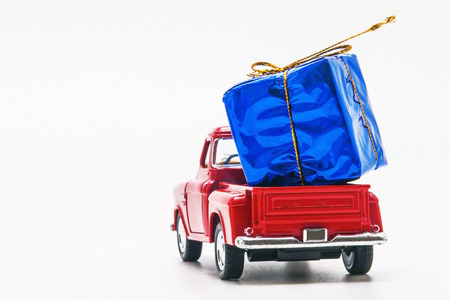 red retro car pickup with a blue gift box isolated. Stock Photo