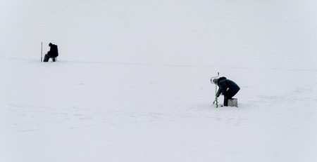 lejos: landscape fisherman on winter fishing far view. Foto de archivo