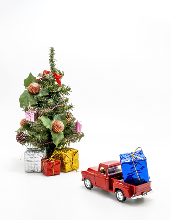 red retro car toy carries a box with a gift for Christmas tree.