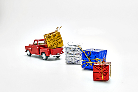 strewed: red retro car toy strewed boxes with gifts isolated. Stock Photo