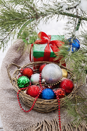 decorated Christmas tree in a snowy forest, sledges, blanket and a basket of toys.