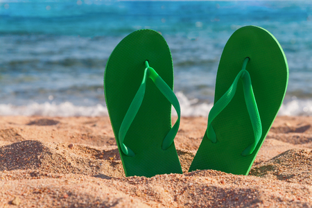 green flip flops in the sand near the sea. Stock Photo