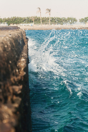 the waves strike the stone pier in blurring.