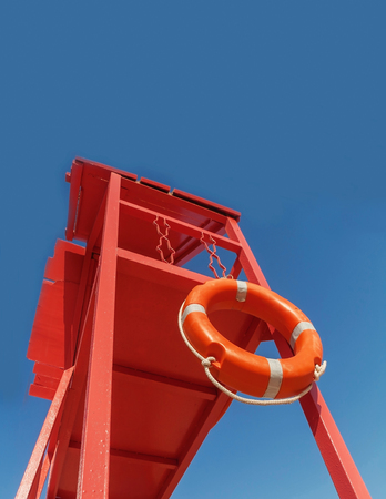 red rescue tower with a lifeline against the blue sky.