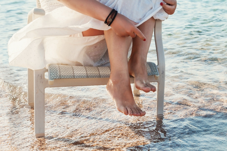 puget: Bare legs girl in a white dress touched the sea water..
