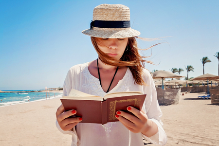 Young adult woman with a hat on the beach reading a book.