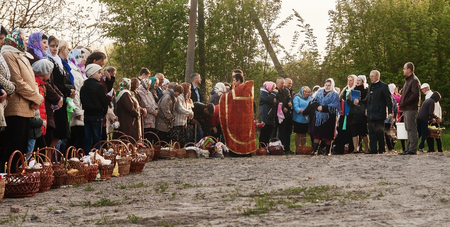 At Easter, the priest blesses the people with baskets and candles. Ukraina.Fastov. May 1, 2016.