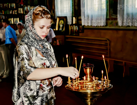 Young woman in church puts a candle and pray.