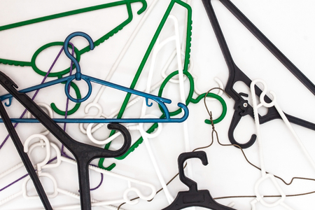 Many hangers of different shapes and colors, top view, white background.