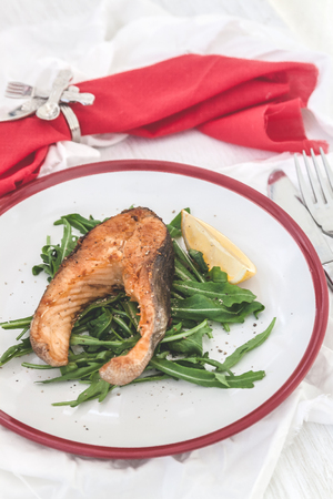 Baked steak trout fish on green leaves of rucola lettuce, lemon, served on white plate serving, top view.