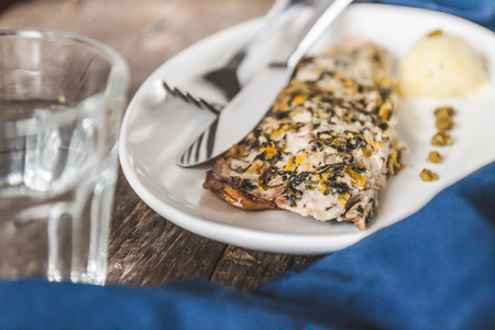 pure de papa: Fish mackerel baked with herbs, mashed potatoes, pesto sauce served on a white plate on a wooden antique background, next to a blue towel-napkin and a glass of water. Top view, close-up Foto de archivo