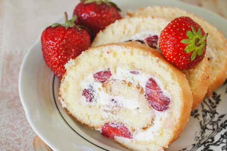 Sponge roulades with cream and fresh strawberries, close-up.