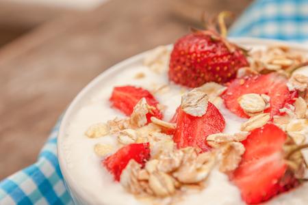 In a cup of yogurt, oat granola and fresh strawberries, on a blu