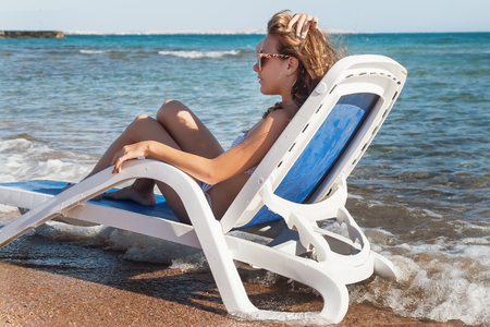 laying forward: Pensive young woman in sunglasses is sitting in a deckchair, against the background of the sea and tropical beach with palm trees. Stock Photo