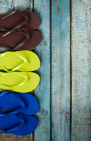 Meerdere paren multi-gekleurde rubberen flip-flops tentoongesteld in een rij op een blauwe houten achtergrond.
