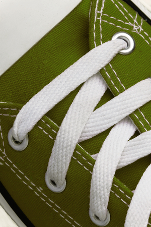 Lacing on a retro sneaker, close-up, on a blue wooden background.