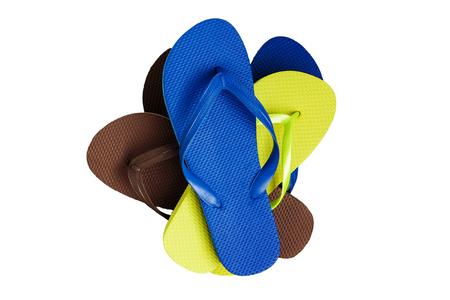 A stack of several pairs of multi-colored rubber flip-flops, isolated.