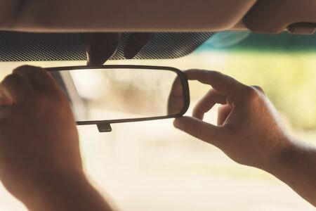 woman mirror: mans hand corrects the rear-view mirror in the car, retro toning.