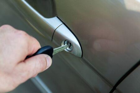 door handle: mans hand opens the car door with a key.