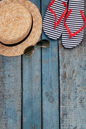 aviators: Still life of different items for relaxing on the beach, rubber flip-flops, hat, camera, phone, sunglasses, headset on a wooden blue background. Concept of a youth trip, rest on the beach with perfumed gadgets. Stock Photo