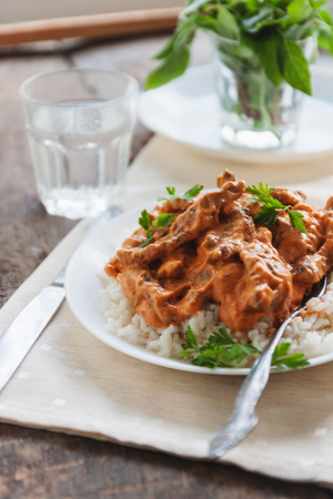 Dish rice with beef stroganoff on a white plate. Stock Photo