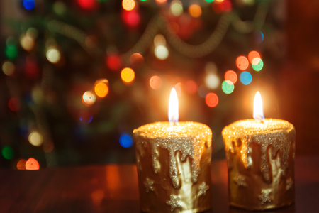 christmas candle in front of a christmas tree with sparkling lights and copy space stock photo