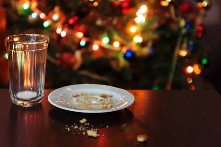 empty glass from milk and crumbs from cookies for Santa Claus under the Christmas tree with lights, close-up.