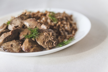 stewed chicken liver and buckwheat porridge on a white tablecloth, in retro toning. Stock Photo
