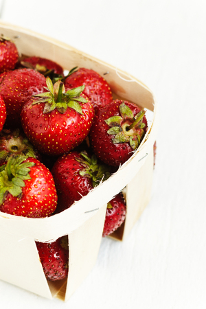 Delicious ripe strawberry in wooden basket isolated on white background.