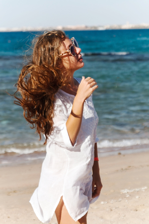 close-up portrait of a beautiful young brunette girl with long hair on a background of blue sea with waves and sky with clouds on a sunny day, lifestyle, posing and smiling, wind.