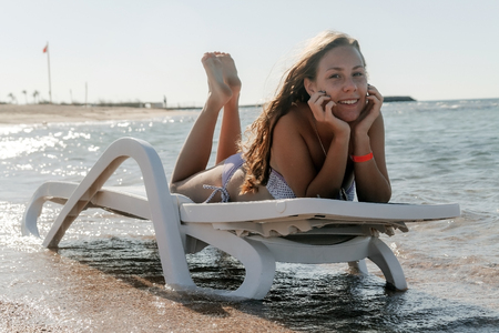Young woman in chaise lounge at the sea beach. Girl relax on beach.