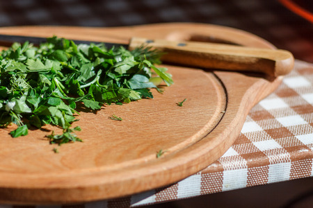 Chopped greens with knife on cutting board.
