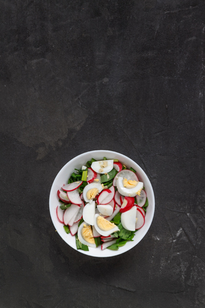 Vegetable vegan salad of ramson, radish, green onions and boiled eggs in a white plate on a dark concrete background, in retro treatment. Close-up, top view, flatlay. The concept of healthy nutrition Banco de Imagens - 102696036