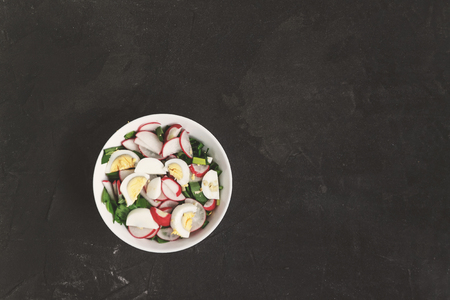 Vegetable vegan salad of ramson, radish, green onions and boiled eggs in a white plate on a dark concrete background, in retro treatment. Close-up, top view, flatlay. The concept of healthy nutrition Banco de Imagens - 106146074