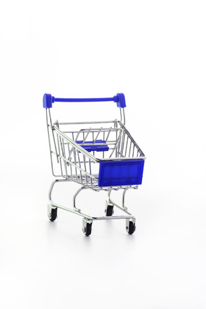 Close up of supermarket grocery push cart for shopping with black wheels and plastic elements on handle isolated on white background. Concept of shopping. Copy space for advertisement Archivio Fotografico