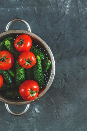 raw whole washed tomatoes and cucumbers in a colander on a dark concrete background. View from above. Flat lay. Archivio Fotografico